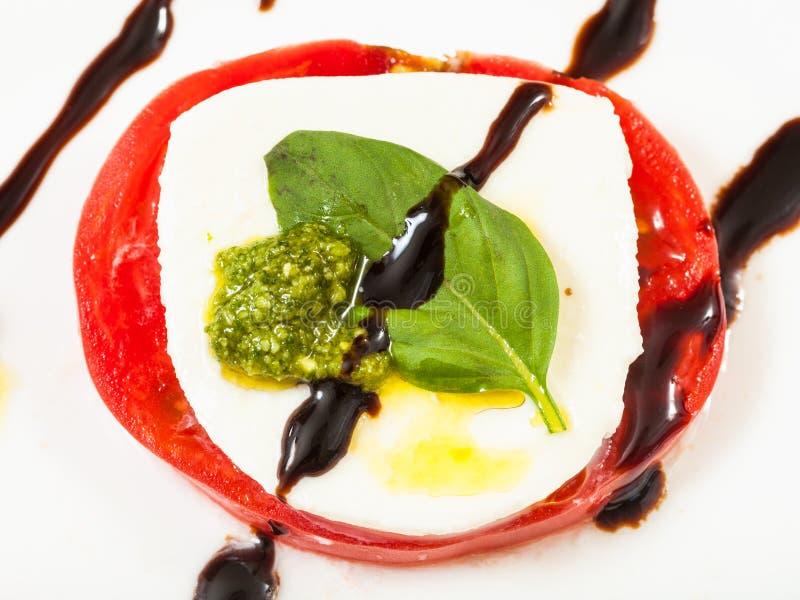 Rebanadas de la mozzarella y del tomate con cierre de la albahaca para arriba imagen de archivo