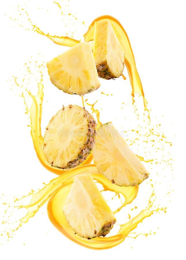 Rebanadas de la piña en el chapoteo del jugo aislado en un fondo blanco foto de archivo