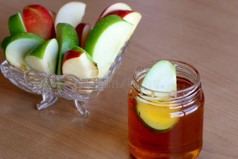 Rebanadas de manzanas y un tarro de miel fotografía de archivo