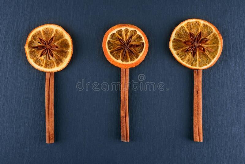 Rebanadas de naranja secada con anís de estrella y la especia del canela en fondo oscuro Las especias se alinean bajo la forma de imagen de archivo