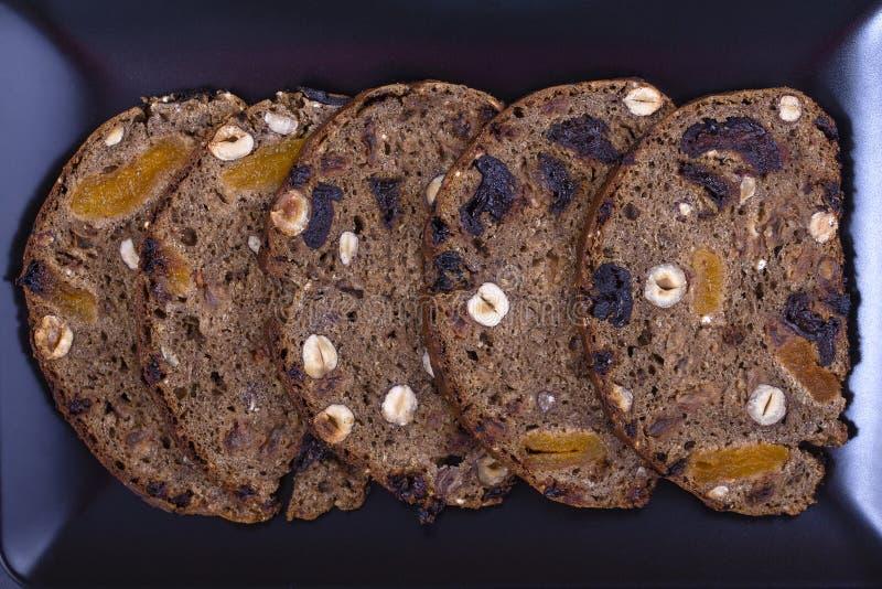 Rebanadas de pan ácimo de granos enteros con de las pasas, nuts y secado, cierre los albaricoques para arriba imagenes de archivo