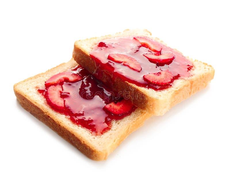 Rebanadas de pan con la mermelada de fresa deliciosa en el fondo blanco imagenes de archivo