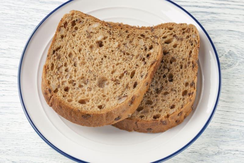 Rebanadas de pan del grano con el molde En una placa blanca con una raya azul En un vector de madera fotografía de archivo