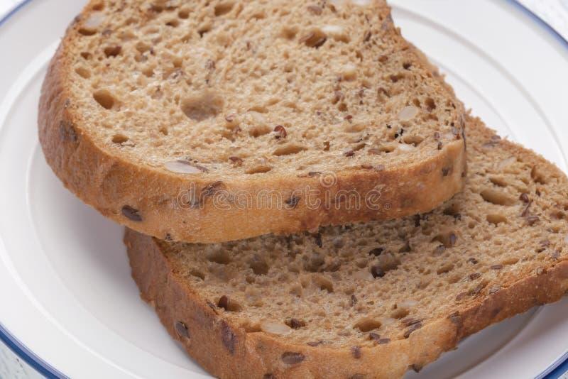 Rebanadas de pan del grano con el molde En una placa blanca con una raya azul En un vector de madera fotos de archivo
