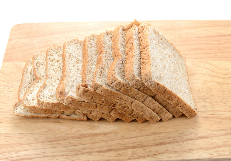 Rebanadas de pan del salvado en el tablero de madera aislado en el backgroun blanco foto de archivo