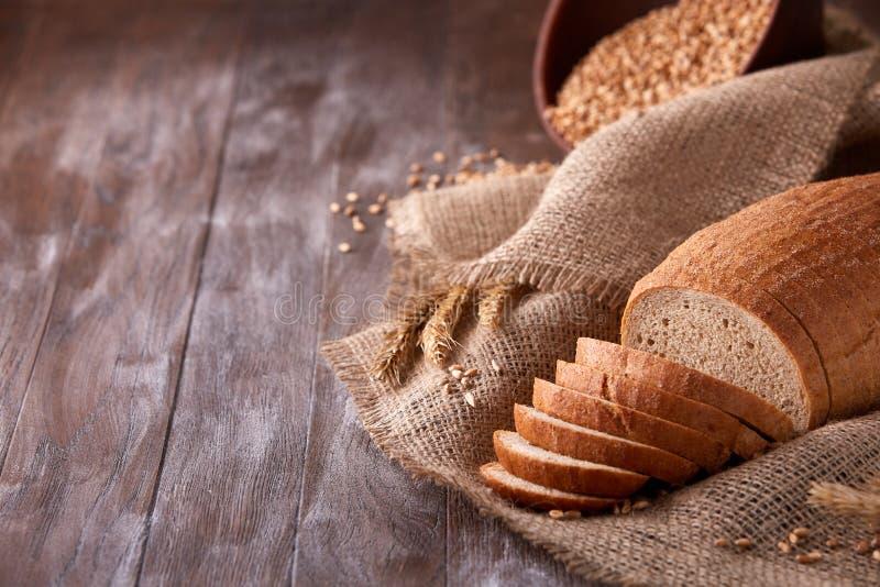 Rebanadas de pan en la arpillera en la tabla de madera la composición con los oídos del trigo dispersó alrededor y los oídos del  fotografía de archivo libre de regalías