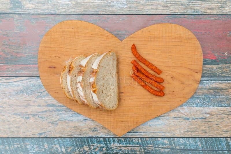 Rebanadas de pan fresco y de salchicha seca del humo en la tabla de madera foto de archivo libre de regalías