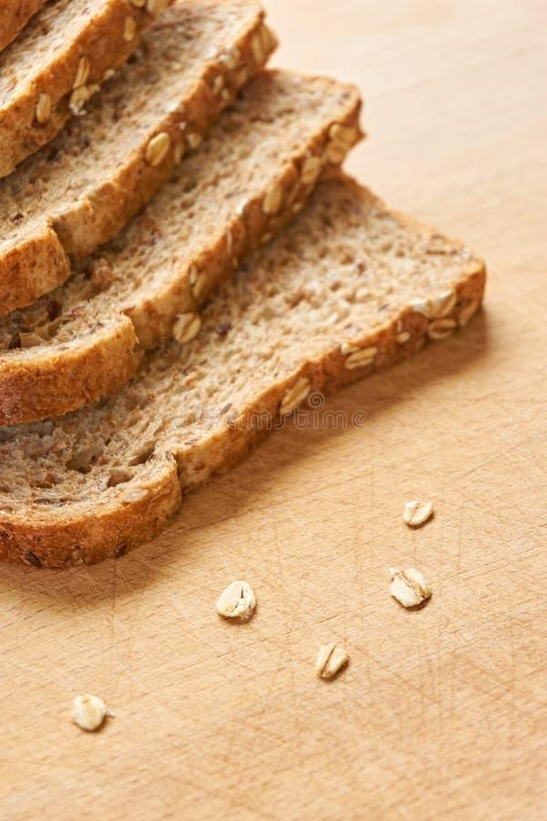 Rebanadas de pan integral en una tabla de cortar de madera imagenes de archivo