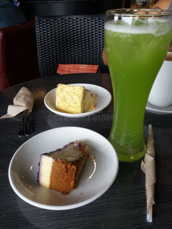 Rebanadas de pastel de queso del arándano y de torta del tiramisu en las placas de cerámica blancas con el vidrio alto de la bebi imágenes de archivo libres de regalías