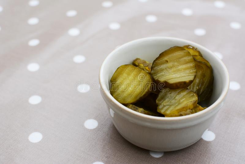 Rebanadas de pepinillos jugosos, amargos en un pote de cerámica foto de archivo