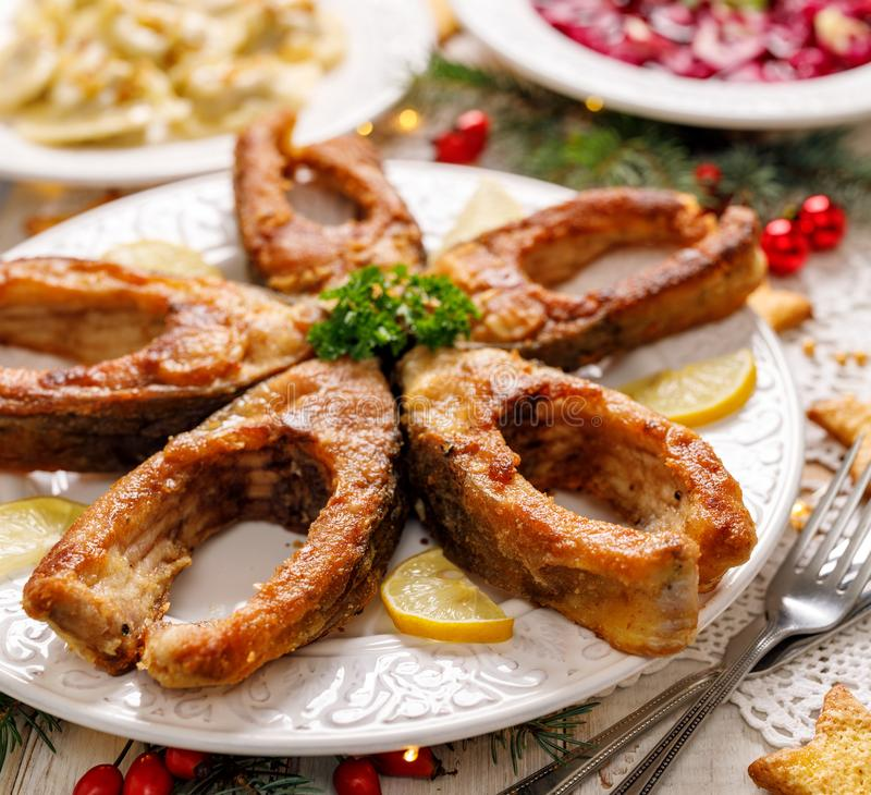 Rebanadas de pescados fritas de la carpa en una placa blanca, cierre para arriba Plato tradicional de la Nochebuena fotografía de archivo