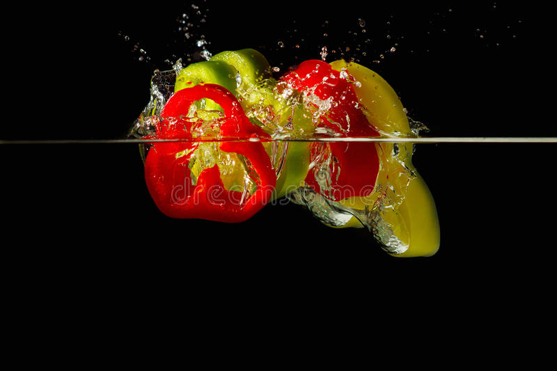 Rebanadas de pimientas rojas y verdes que caen en agua imagen de archivo libre de regalías