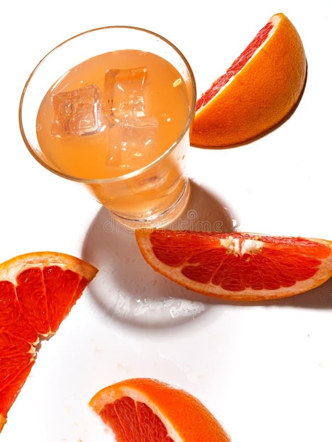 Rebanadas de pomelo jugoso y de un vidrio de limonada fresca con hielo en un fondo blanco imágenes de archivo libres de regalías