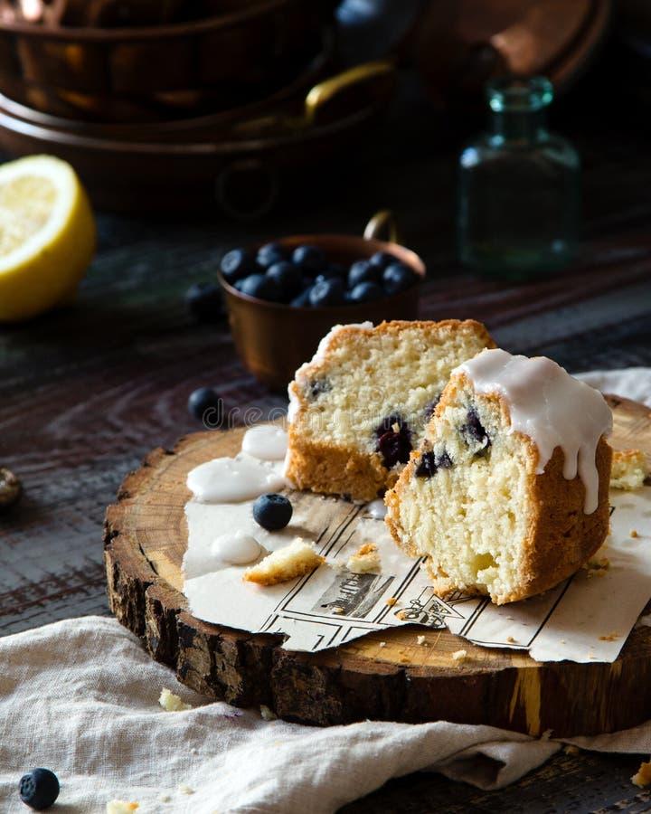 Rebanadas de torta deliciosa hecha en casa del bundt con el esmalte blanco en el top en soporte de madera imagenes de archivo