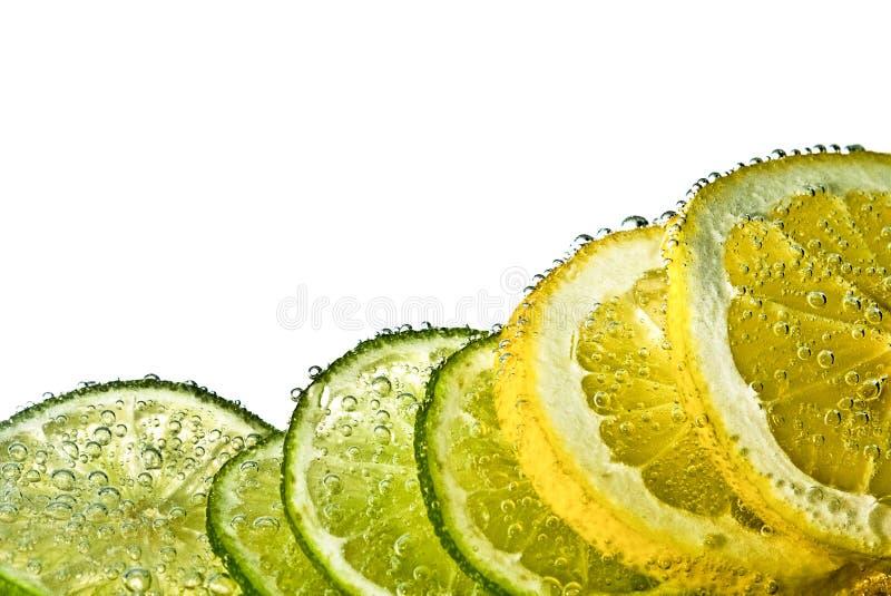Rebanadas del limón y de la cal en agua foto de archivo libre de regalías