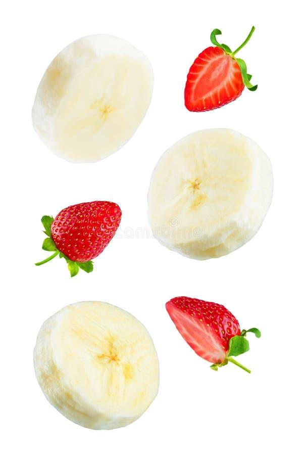 Rebanadas del plátano que vuelan con las fresas en un fondo blanco fotografía de archivo libre de regalías