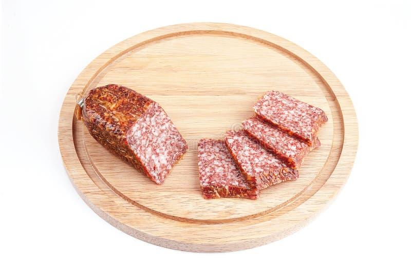 Rebanadas del salami en tarjeta de madera fotografía de archivo libre de regalías