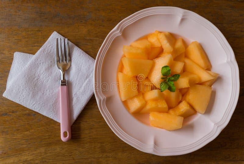 Rebanadas frescas del melón en plato fotos de archivo