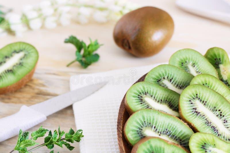 Rebanadas jugosas del kiwi en una placa de madera en el primer de la tabla, madera deliciosa de la fruta, productos dietéticos, i imagen de archivo libre de regalías