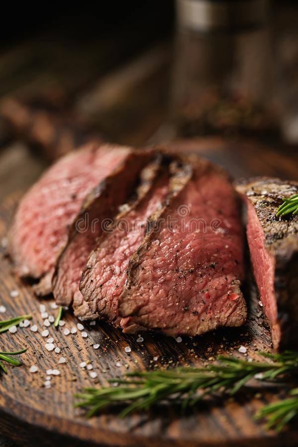 Rebanadas medias jugosas del filete de Rib Eye de la carne de vaca en el tablero de madera con las especias y la sal de las hierb foto de archivo