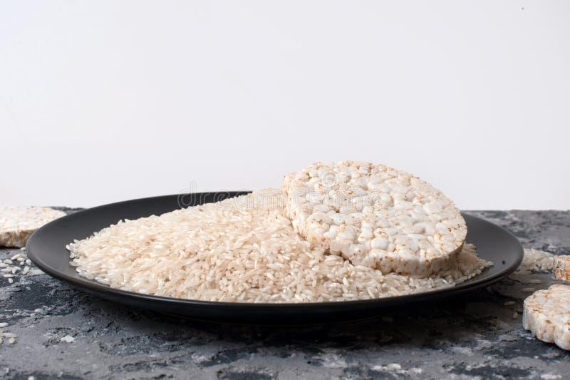 Rebanadas sanas del pan del arroz en la placa negra en el fondo blanco imagen de archivo