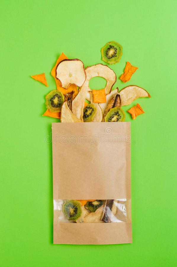 Rebanadas secadas de las frutas y verduras en bolsa de papel del arte en fondo verde fotografía de archivo libre de regalías