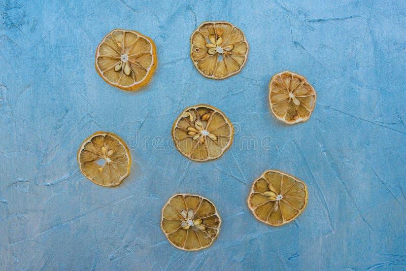 Rebanadas secadas del limón en un fondo azul Cuñas de limón cortadas Cocinar la compota o el jugo de los frutos secos Preparar té fotos de archivo
