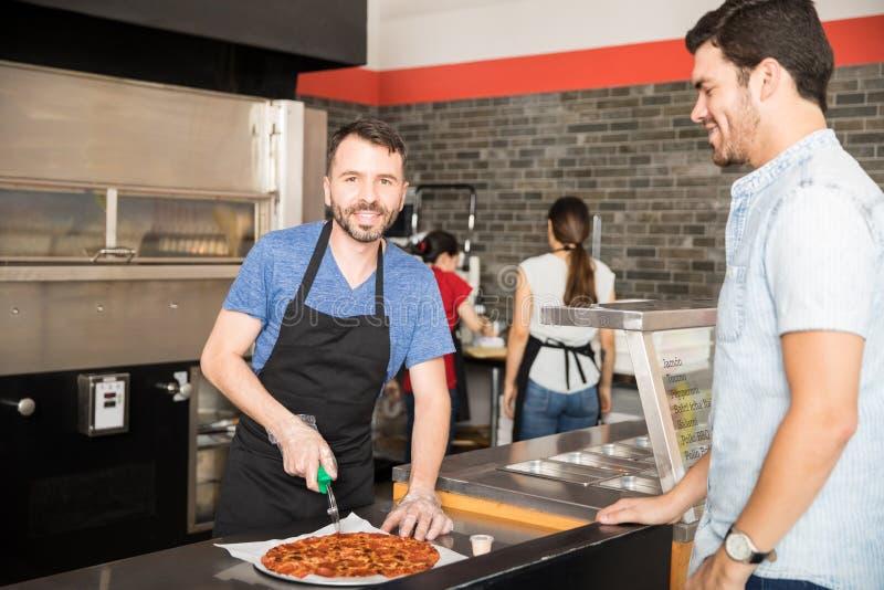 Rebanadas sonrientes de la pizza del corte del cocinero en el contador delante del custume fotos de archivo libres de regalías