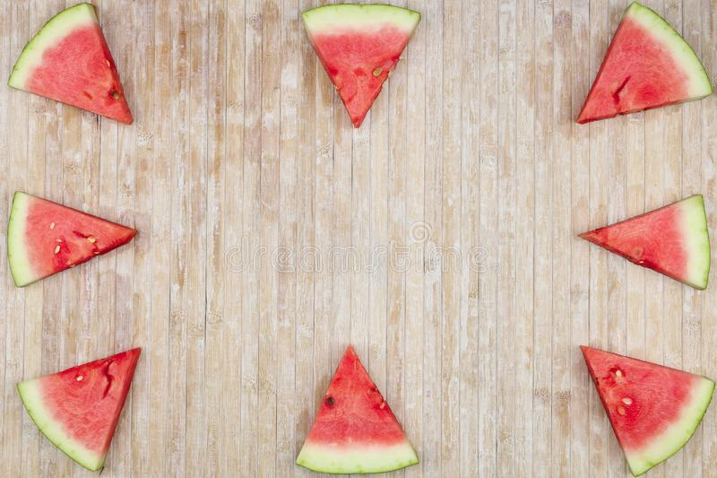 Rebanadas triangulares de sandía que forman los juegos geométricos para el espacio de la copia en un fondo de madera ligero fotos de archivo libres de regalías