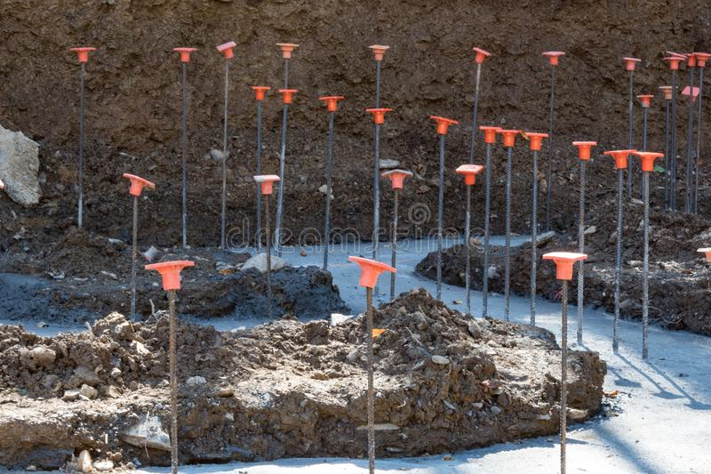 Rebar with orange safety caps protruding from poured concrete footings stock image