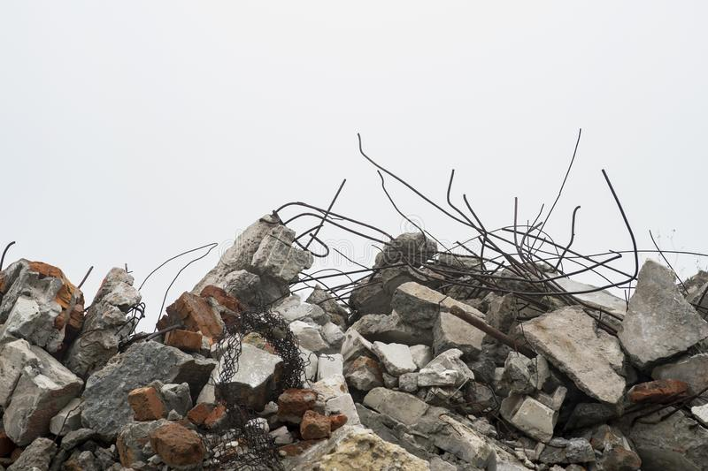 The rebar sticking up from piles of brick rubble, stone and concrete rubble against the sky in a haze. Remains of the destroyed building. Copy space royalty free stock photos