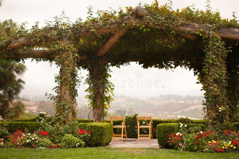 Rebe abgedeckter Patio und Stühle mit Land-Ansicht lizenzfreies stockfoto