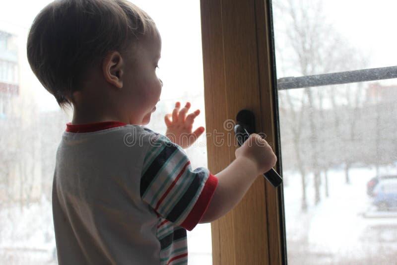 Rebecca 36 een kind bevindt zich op de venstervensterbank en probeert aan stock foto's