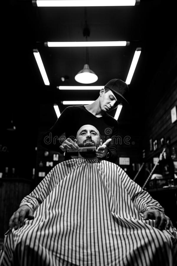 Rebecca 36 Il parrucchiere alla moda Il barbiere di modo riordina la barba dell'uomo brutale che si siede nella poltrona fotografia stock