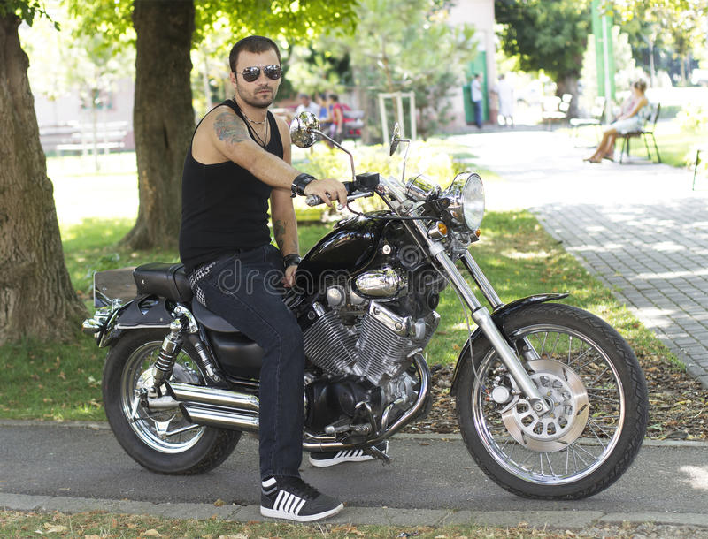 Rebel young man on a motorcycle royalty free stock photos