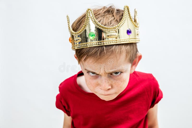 Rebellious spoiled kid with crown for mad attitude, high angle royalty free stock image