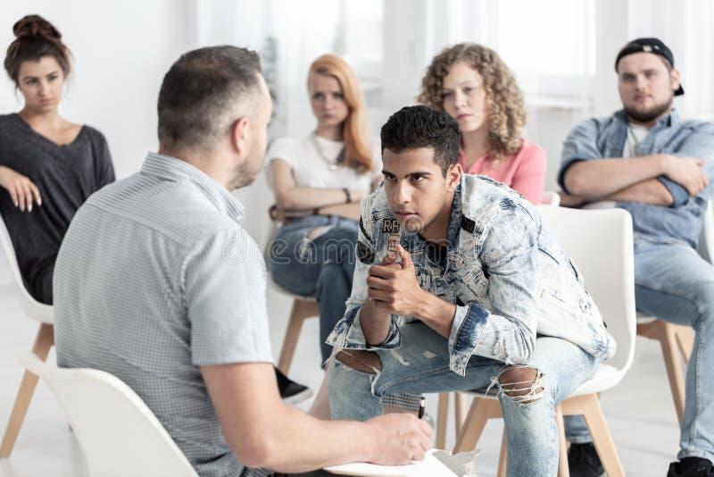 Rebellischer spanischer Mann, der auf Psychologen während der Gruppentherapie auf Jugendliche hört stockfotos