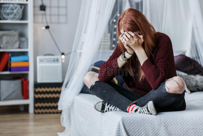 Rebellisches Mädchen, das auf Bett schreit lizenzfreie stockfotografie