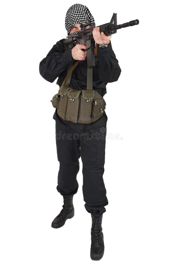 Rebellisk iklädd svart likformig och svartvit shemagh med geväret för anfall m4 royaltyfri fotografi