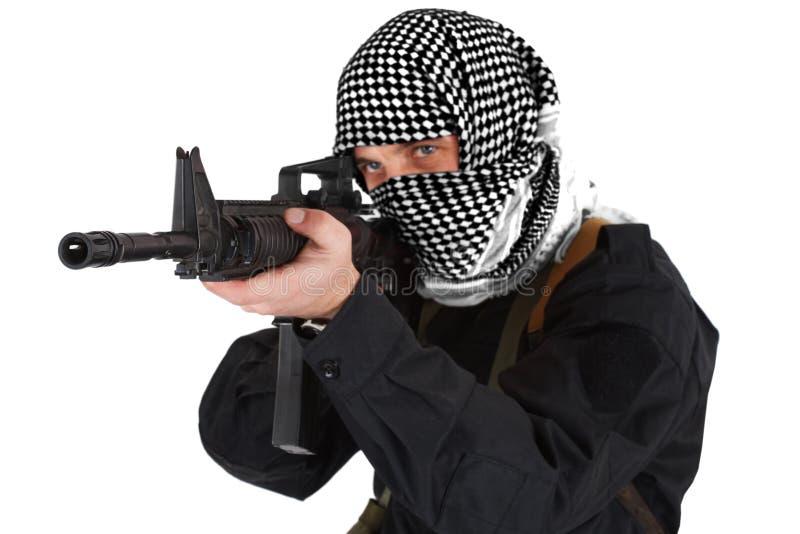 Rebellisk iklädd svart likformig och svartvit shemagh med geväret för anfall m4 royaltyfria foton