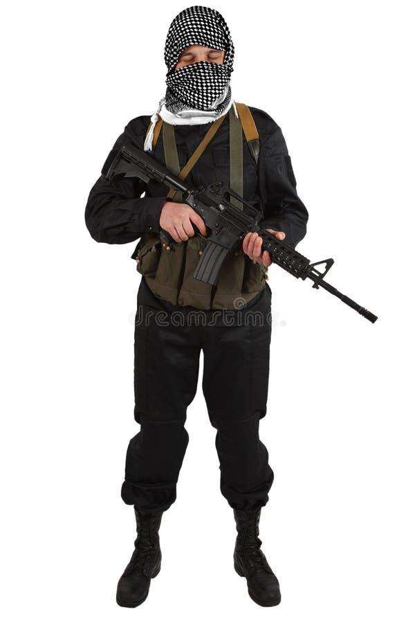 Rebellisk iklädd svart likformig och svartvit shemagh med geväret för anfall m4 royaltyfria bilder