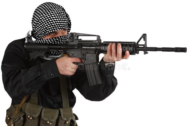 Rebellisk iklädd svart likformig och svartvit shemagh med geväret för anfall m4 fotografering för bildbyråer