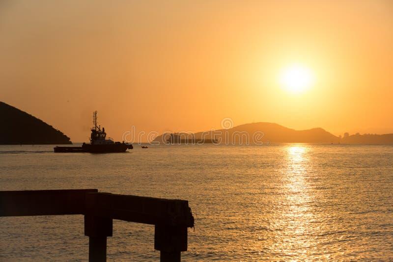 Rebocador que vai buscar um navio durante o por do sol foto de stock