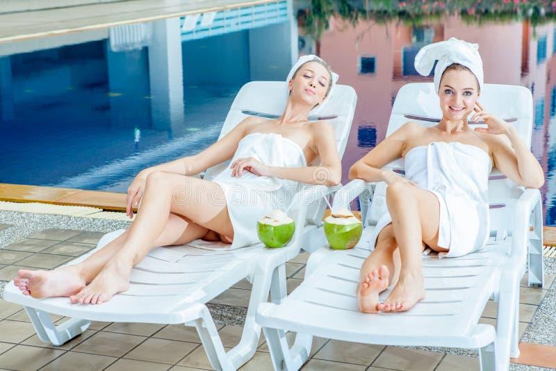 Reboque jovens mulheres bonitas envolveu a toalha branca que encontra-se na cama do sol foto de stock