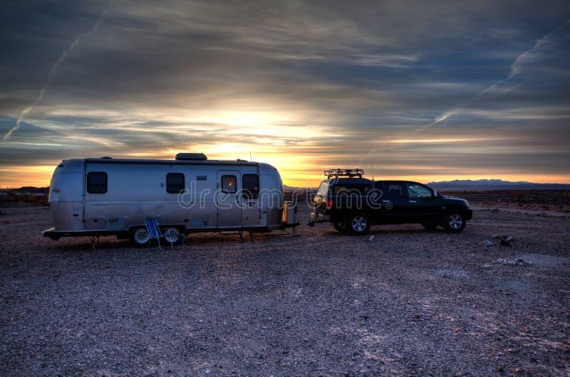 Reboque retro do curso da corrente de ar estacionado no acampamento do deserto de Califórnia imagem de stock royalty free