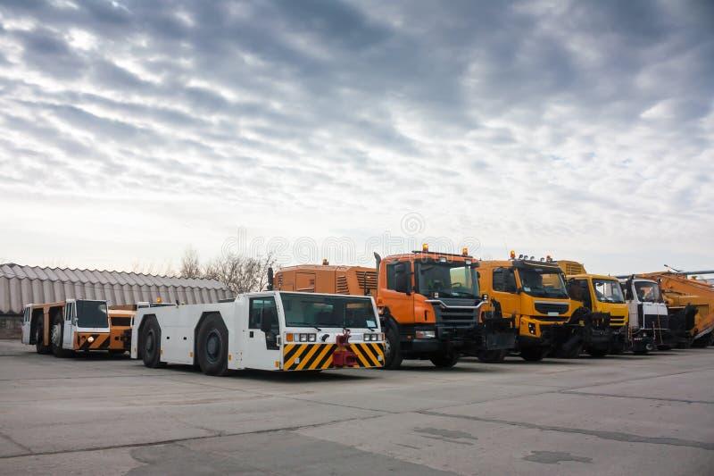 Reboque tratores e caminhões da limpeza no aeroporto fotografia de stock