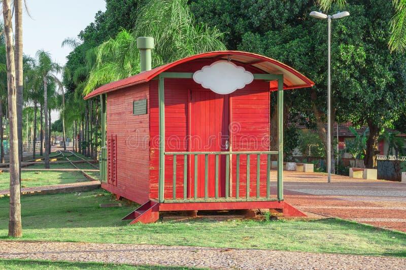Reboque vermelho através do parque com a trilha railway velha, os alguns bancos e muita natureza do árvore e a verde ao redor Pla imagens de stock royalty free