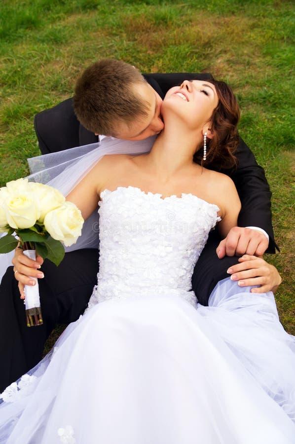 Recém-casados bonitos colocados na grama fotografia de stock royalty free
