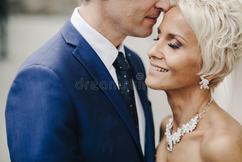 Recém-casados de sorriso felizes que andam fora, beijando e abraçando fotografia de stock