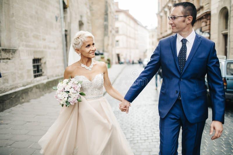 Recém-casados de sorriso felizes que andam fora, beijando e abraçando imagens de stock royalty free